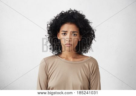 Frustrated Young Dark-skinned Woman With Shaggy Black Hair Frowning, Looking At Camera With Sad And