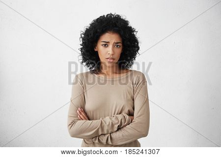 Indoor Shot Of Skeptical Young Mixed Race Woman Feeling Suspicious, Her Look Expressing Disapproval