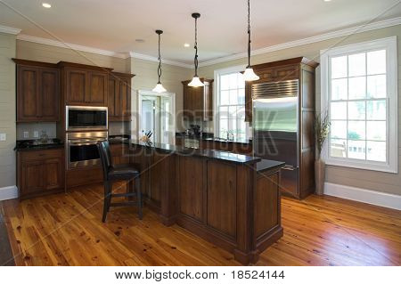 luxury kitchen in affluent home with heart pine floors and granite island