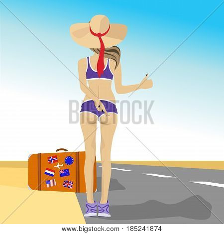 Young woman hitching on highway wearing a straw hat standing next to suitcase