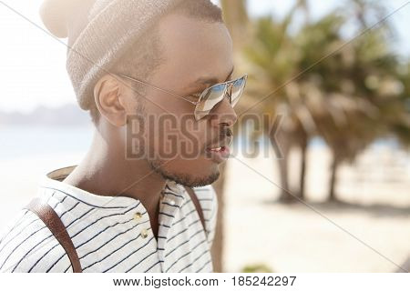 Outdoor Headshot Of Black Attractive And Good-looking Thoughtful Tourist Having Fashionable Look Iso