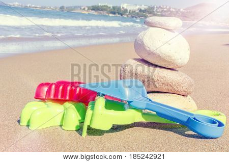 Vacation image of children's beach toys and stones on the sand in beautiful sunny day. Kids summer holidays activity concept. Copy space.