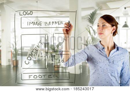 web designer drawing website development wireframe in office