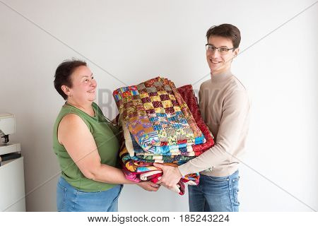 quilting and needlework in the workshop - smiling tailors together holding the finished product, made of colored patchwork fabrics near your desktop with a sewing machine