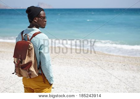 Trendy Looking Young Afro American Traveler Carrying Knapsack Looking At Calm Azure Sea In Front Of