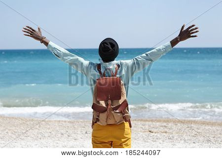 Read View Of Happy Carefree African American Male Standing On Beach In Front Of Azure Sea With His B