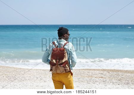 Back Outdoor View Of Young African Male Tourist With Knapsack Wearing Trendy Clothing Spending Sunny