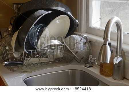A stack of hand washed dishes drying in a dish drain by the sink in the morning sun coming through a window
