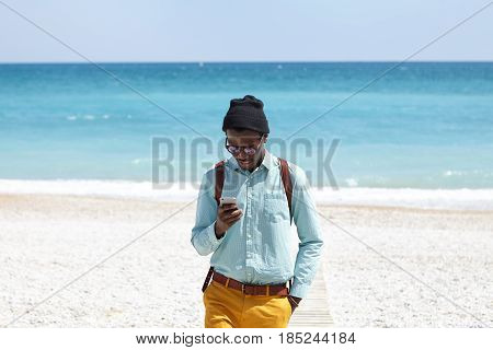 Stylish Dark-skinned Student Carrying Knapsack Wearing Trendy Clothes Standing On Boardwalk After Mo