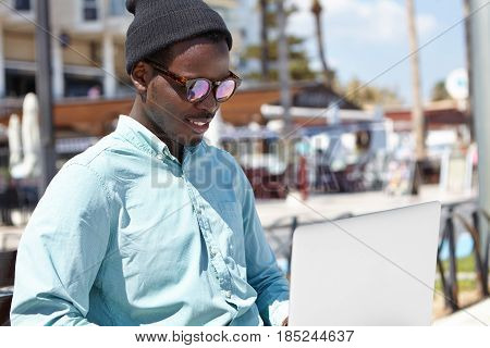 Outdoor Portrait Of Relaxed Young Black Male In Stylish Headwear And Sunglasses Using Notebook Compu