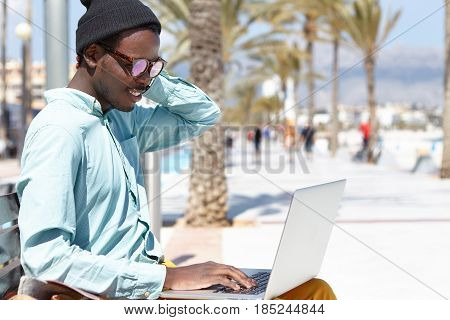 Fashionable Young Afro American Freelancer Wearing Stylish Clothes And Accessories Sitting On Bench,