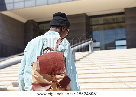 Rear Shot Of Unrecognizable Afro American Male Student Carrying Knapsack Going Upstairs Towards Mode