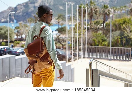 Rear View Of Stylish Afro American Man With Knapsack Standing In Urban Setting With Mountains And Az