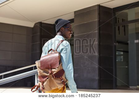 Rear Shot Of Happy African American Man Traveler Carrying Leather Knapsack About To Enter Modern Hot