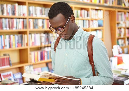 Indoor Shot Of Stylish African American Student In Glasses Looking Through Book In His Hands, Choosi