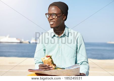 Stylish Trendy Looking Young Afro American Dreamer With Map Sitting On Embankment Against Calm Sea B