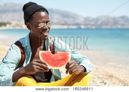 Cheerful African American Student Wearing Hat, Mirror Sunglasses And Knapsack Sitting Cross Legged O