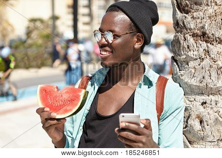 Carefree Trendy Looking Afro American Hipster Holding Slice Of Watermelon In One Hand And Mobile In