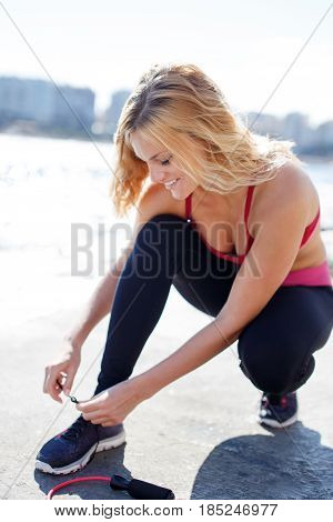 Young sporty blonde woman tying shoelace outdoor at coast