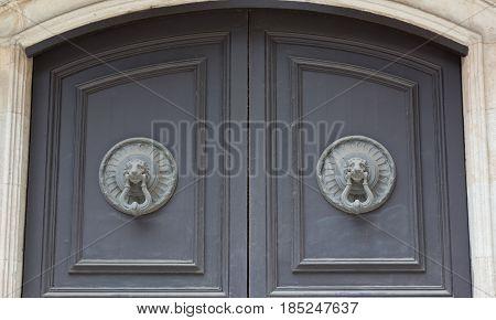 Old wooden door with handle knocker iin the shape of a lion's head Spain Barcelona. Antique wooden door of apartment building outdoor. Horizontal image