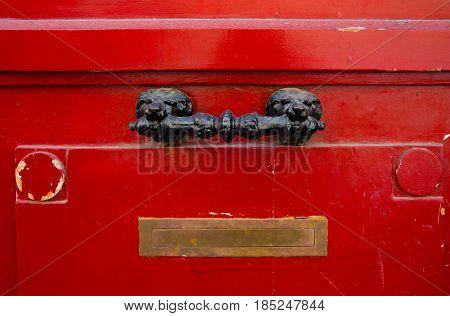 Old red wooden door with decorativel handle and Inbox in Paris France. Antique wooden door of apartment building outdoor. Horizontal image
