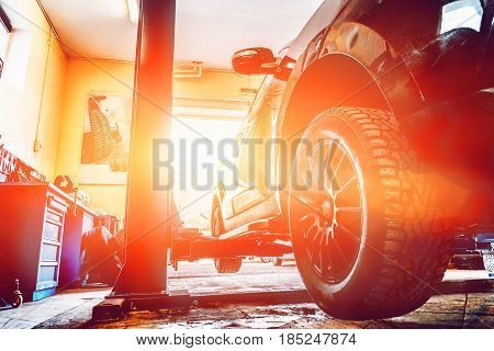 Black car on auto lift in garage for repair and maintenance service, sunlight effect