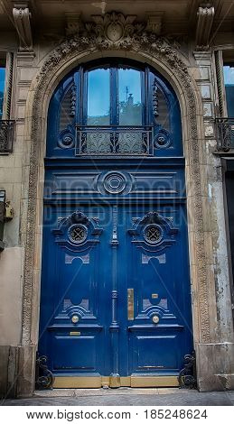 Old Blue carved ornate door in Paris France. Antique wooden door of apartment building outdoor. Vertical image