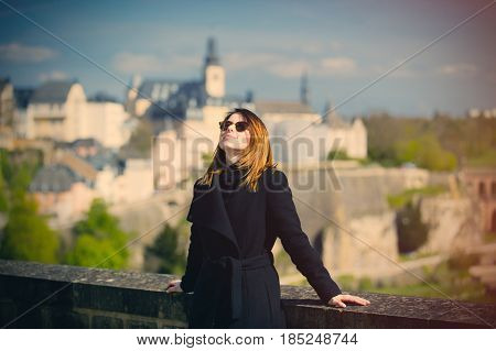 portrait of beautiful young woman relaxing and enjoying a splendid view of town