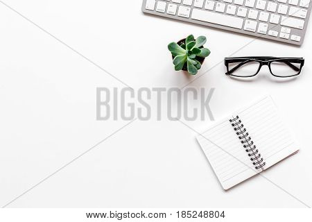 Modern office table with computer keyboard, glasses, notebook on white background top view mock-up