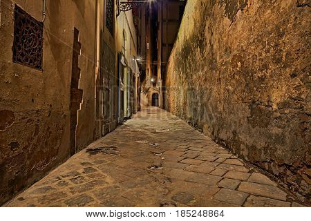 Florence, Tuscany, Italy: dark narrow alley in the old town at night lit by old street lamps