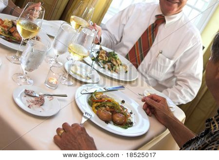 people eating at a business lunch table, focus on the food and wine