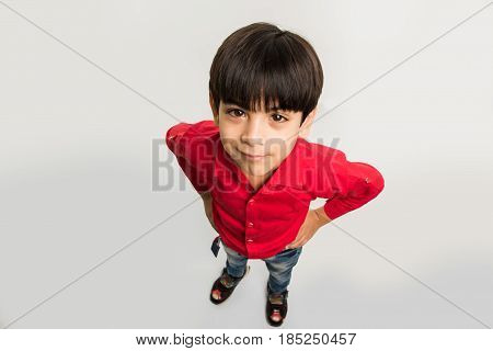 indian smart kid or boy standing over white background and looking upward at camera, top view, isolated over white background