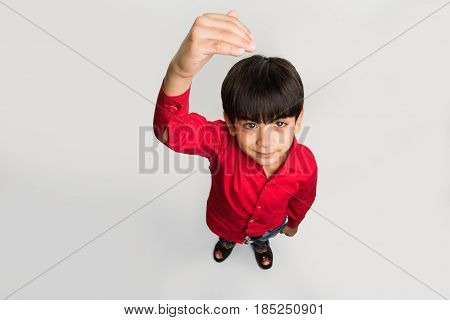indian smart kid or boy standing over white background and showing or measuring his height with hands, looking upwards at camera, top view