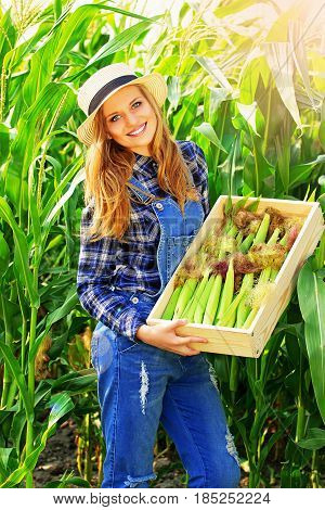 Farming Concept. Portrait Of Young And Beautiful Red Haired Girl In Hat And Coveralls Holding Box Wi