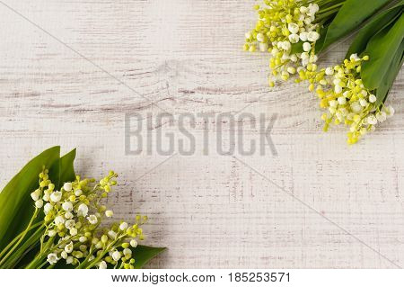 Lily of the valley on gray wooden background for greeting card . Top view with copy space.