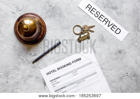 hotel reception desk with booking form and ring on stone background top view