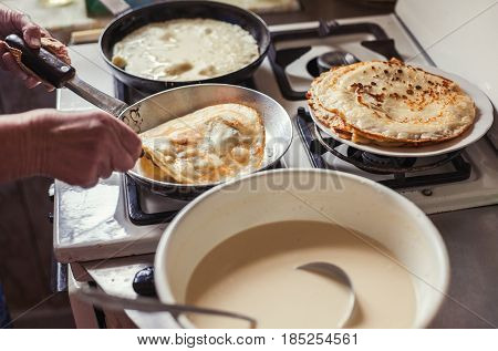 Grandmother making pancakes on the kitchen at home