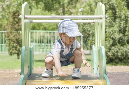 2 year-old boy playing on slider at playground. He is on the top. Balance concept