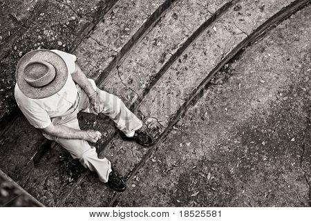 old man sitting on steps alone, hdr image