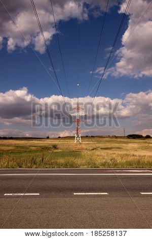 Electric power line and road with sky and clouds
