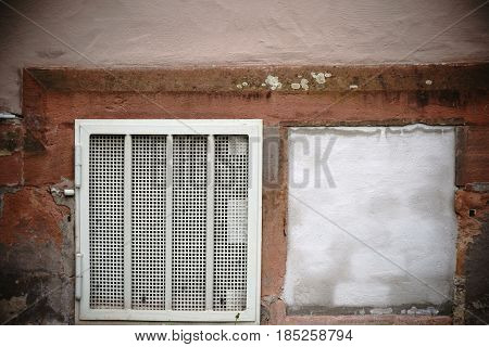 A basement hatch with a lattice and a walled basement hatch on a house wall.