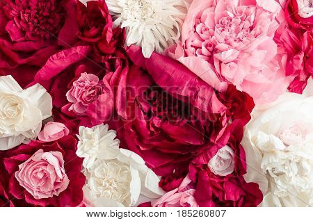 Beautiful artificial paper flowers wall pattern with amazing red pink and white roses peonies. Mothers Day concept background for your design. Mother's gritings card. Directly above. Copy space.