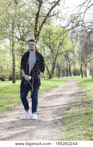 Young Man Walks In The Park, Holding The Phone In His Hand And Listen To Music