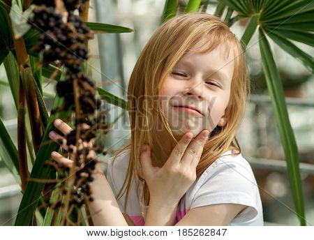 livistona chinensis, portrait, little girl seven years old, sitting next to a palm tree in a botanical garden, long blond, wheat hair, sunny, bright day,funny parody, mimic model, 	amusing,