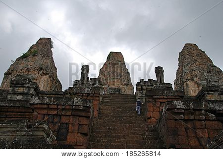 A woman climbing the stairs in a temple of Ankor Wat. Cambodia