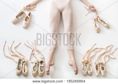Beautiful ballerina lies with stretched legs on the white floor in the studio. She wears a light dance wear and holds ribbons of shoes in the hands. On the sides of her legs there are ballet shoes.