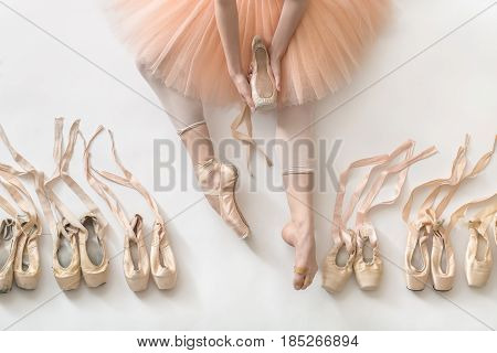 Ballerina sits on the white floor and holds a beige pointe shoe in the studio. She wears a light dance wear and a peach tutu. On the sides there are ballet shoes. Top view photo. Horizontal.