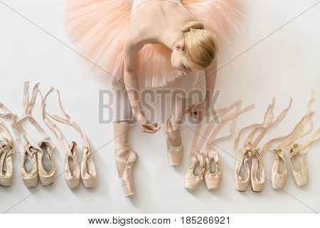 Sensual ballerina sits on the white floor and dresses a beige pointe shoe in the studio. She wears a light dance wear and a peach tutu. On the sides there are ballet shoes. Top view photo. Horizontal.