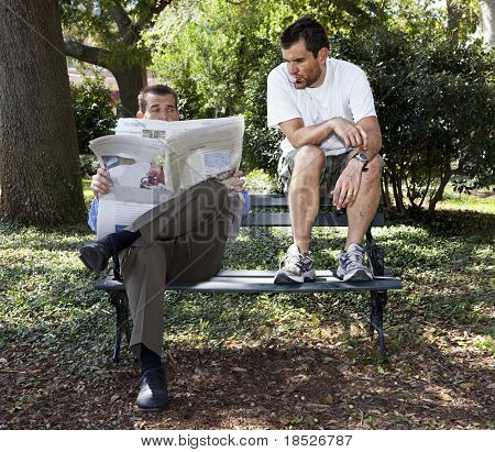 dirty person reading newspaper over businessman's shoulder