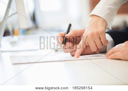 Detail of a man signing a contract and woman showing where to sign